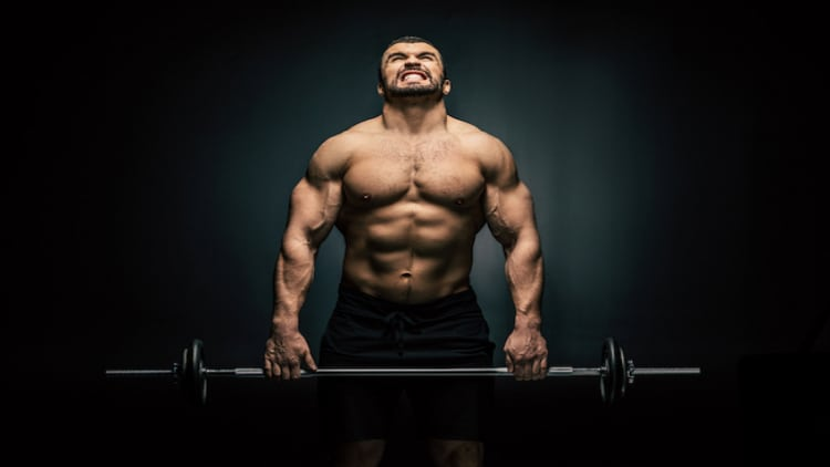 Athletic man gripping onto a heavy barbell