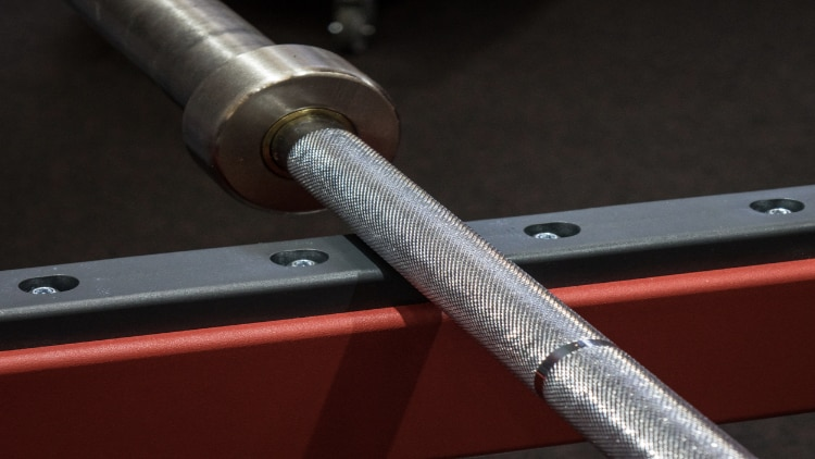 A barbell resting in a power rack