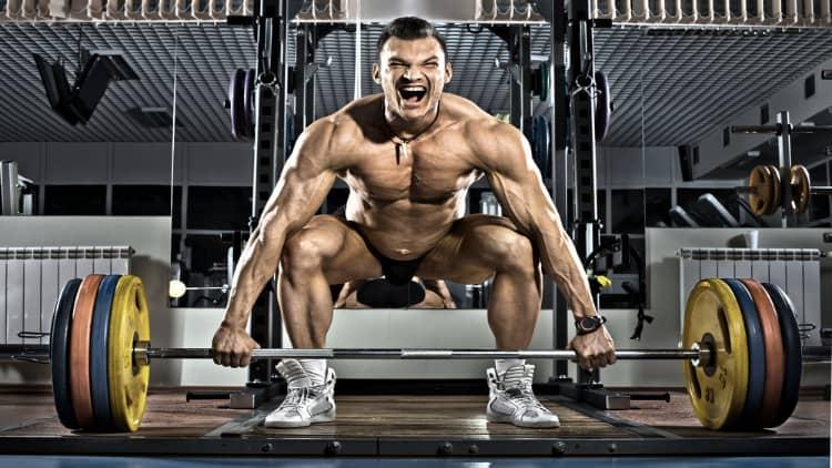 Intense bodybuilder performing wide grip deadlifts