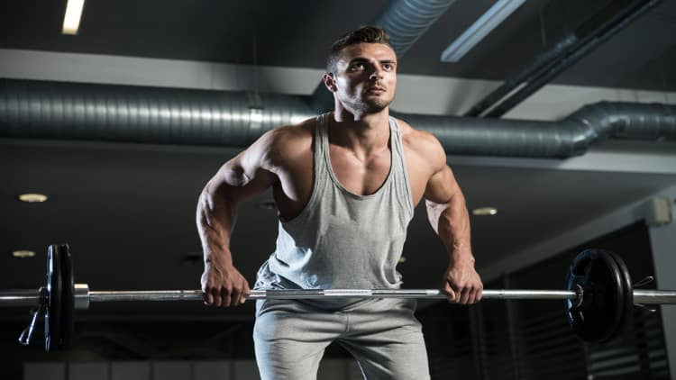 Muscular man doing barbell rows