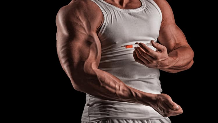 Muscular man pointing a syringe at his arm