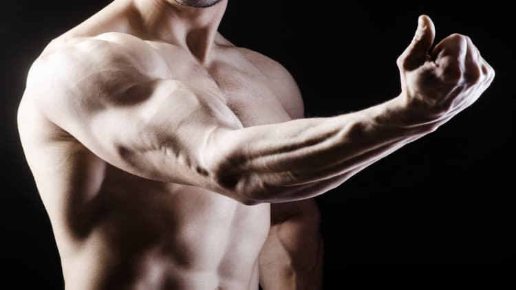 Fitness model flexing his arm