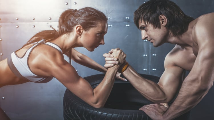 A man and a woman arm wrestling