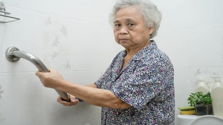 Asian senior woman holding a handrail