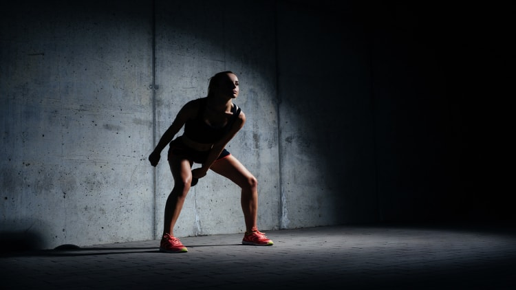 Athletic woman swinging a kettlebell