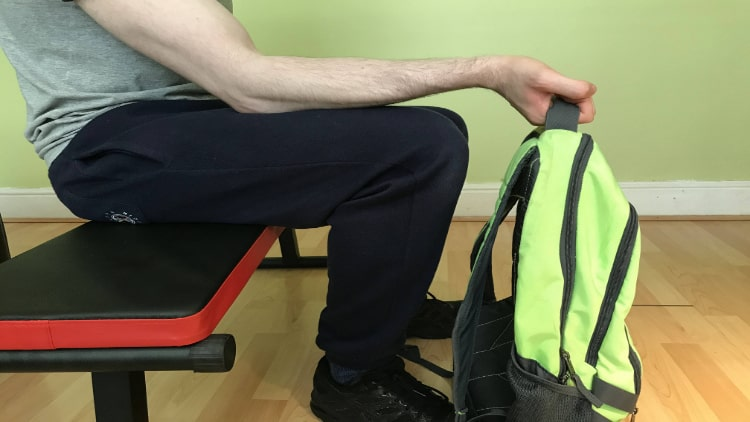 A man performing a backpack wrist curl