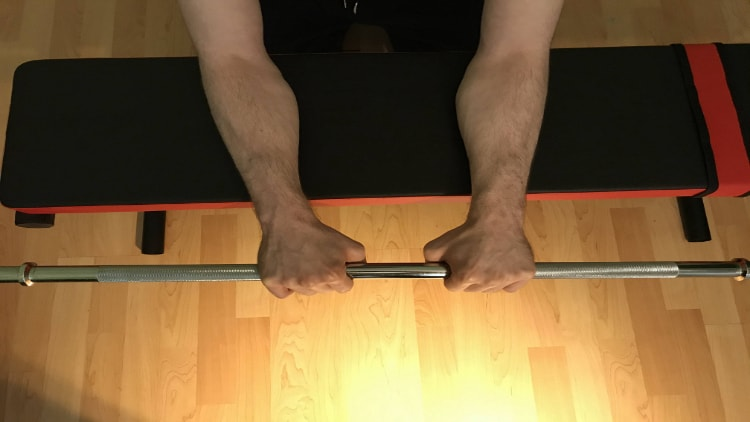 A person doing a close grip barbell reverse wrist curl