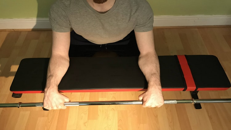 A person doing a reverse barbell wrist curl over a bench