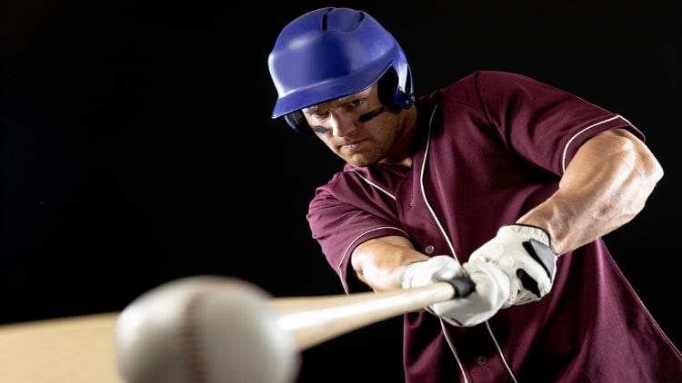 Baseball player hitting the ball with his bat