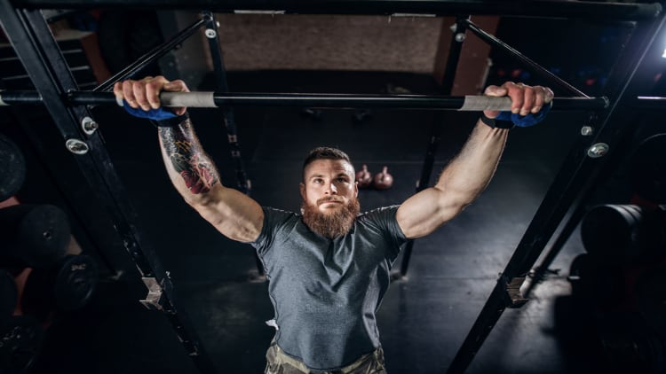 A bearded man performing pull ups