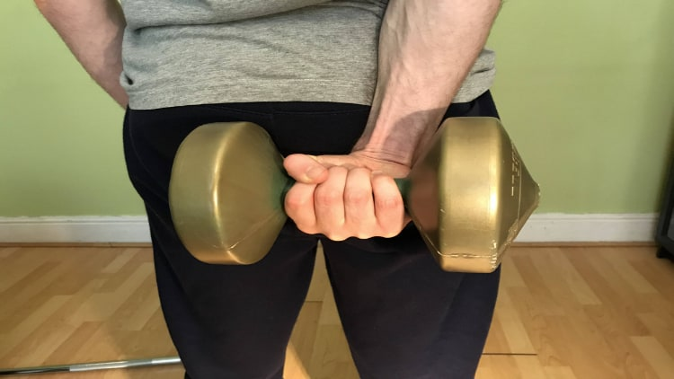 A person performing a dumbbell behind the back wrist curl
