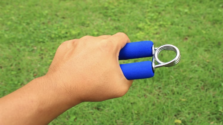 Man using a grip strengthener device outside