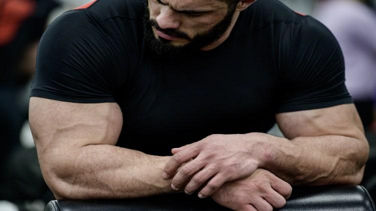 Bodybuilder looking at his massive biceps