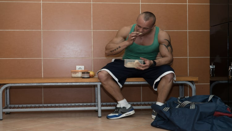 Bodybuilder eating from a plastic contrainer