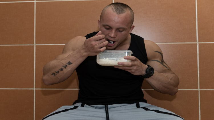 Bodybuilder eating his food out of tupperware