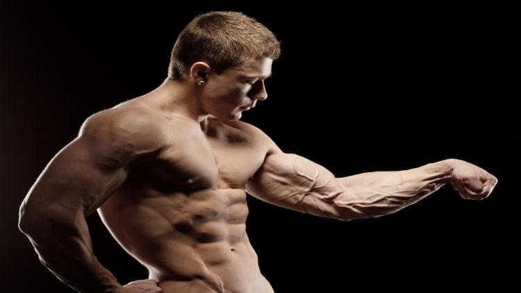 Fitness model flexing his forearm