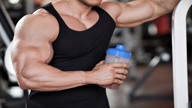 Bodybuilder with jacked forearms holding a protein shake
