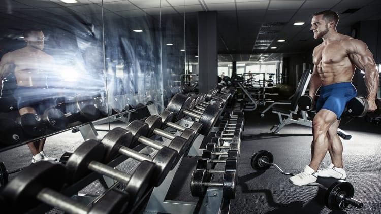 Shirtless bodybuilder looking in the gym mirror