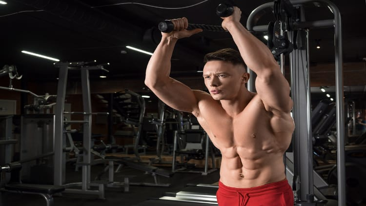 Ripped man performing a cable triceps extension