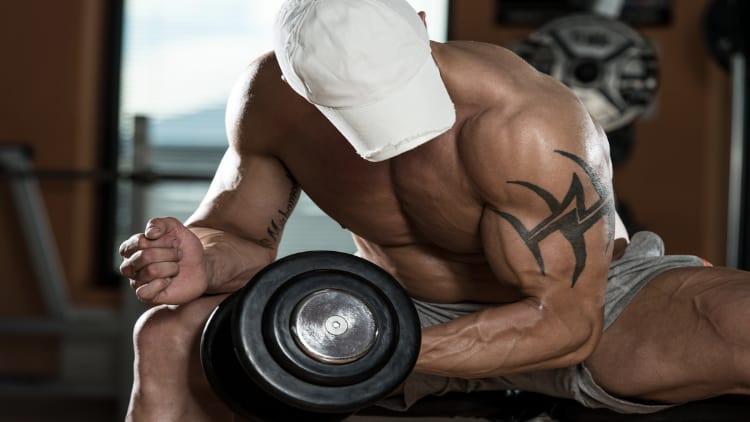 Shirtless man performing a seated concentration curl