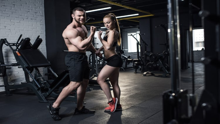 A fit couple flexing at the gym