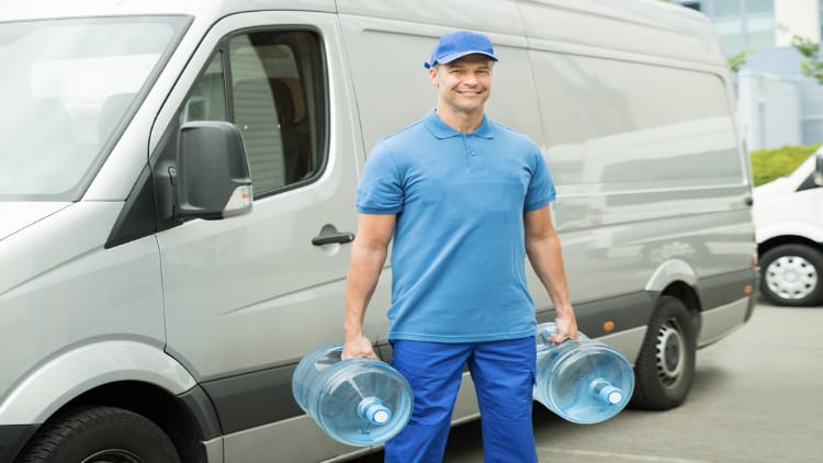 A delivery man holding two large water bottles