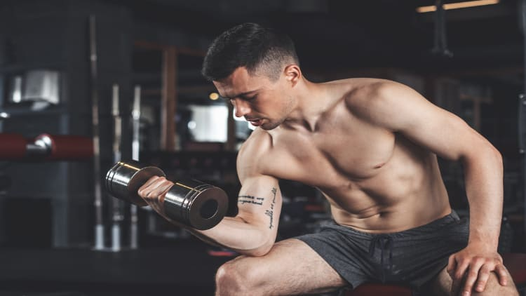 Man doing a dumbbell curl while sat down