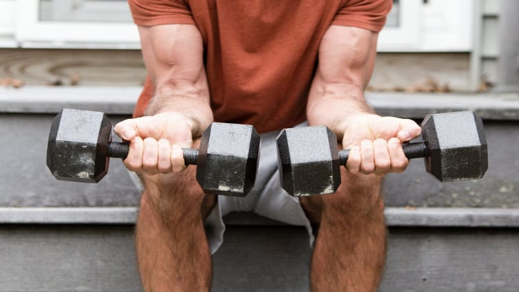 Man performing a seated dumbbell forearm curl