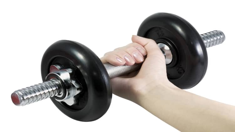A woman holding a dumbbell in her hand