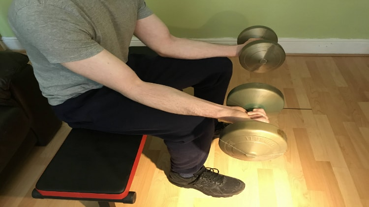 A person doing the dumbell wrist curl exercise