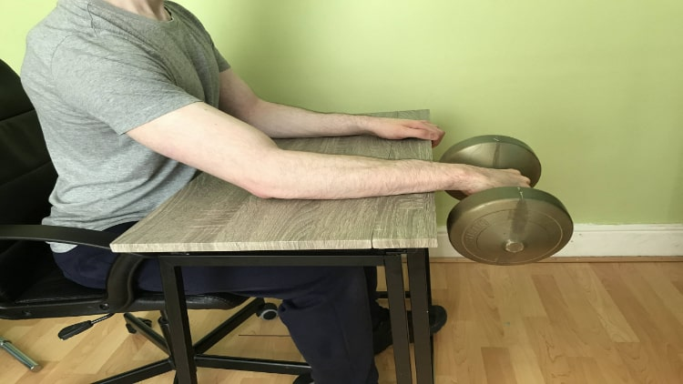 A man doing a dumbbell wrist extension over a desk