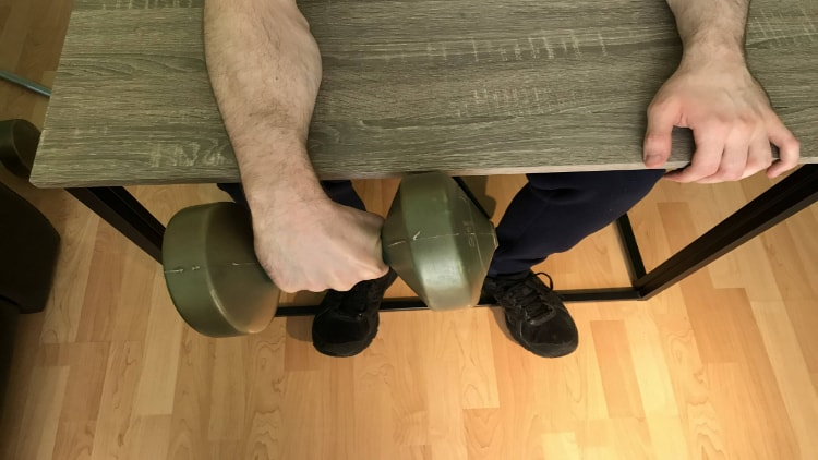 A man doing dumbbell wrist extensions