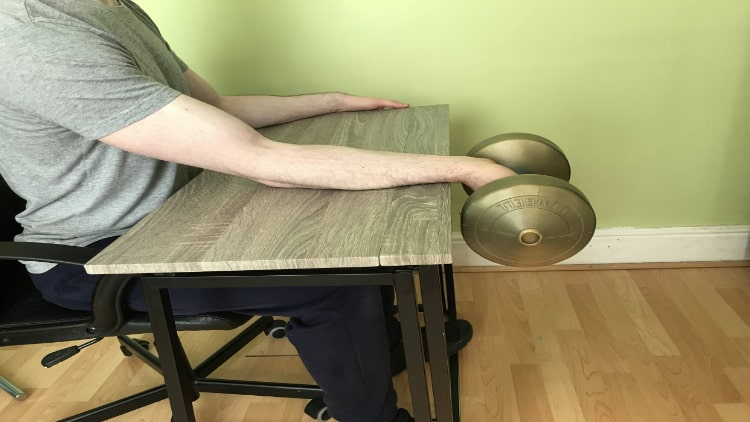 A man performing a dumbbell wrist flexion over his desk