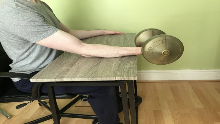 A man doing a dumbbell wrist flexion exercise