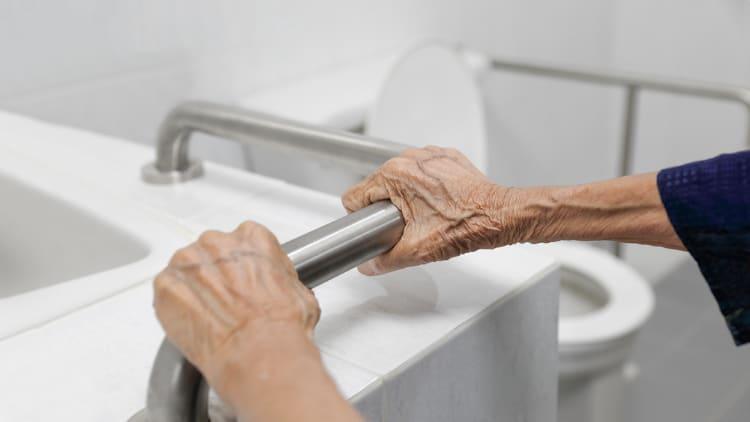 Senior woman holding a bathroom handrail