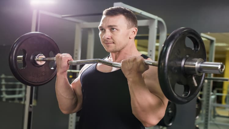 A man performing EZ curls in the gym