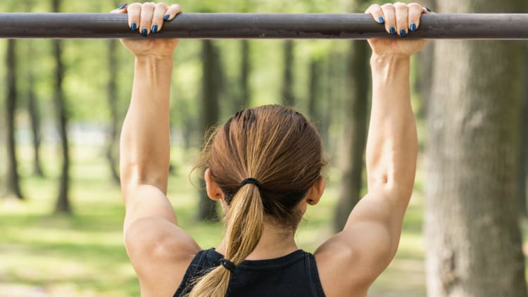 Strong woman doing chin ups outside