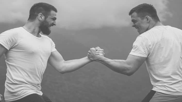 Two men giving each other a very firm handshake