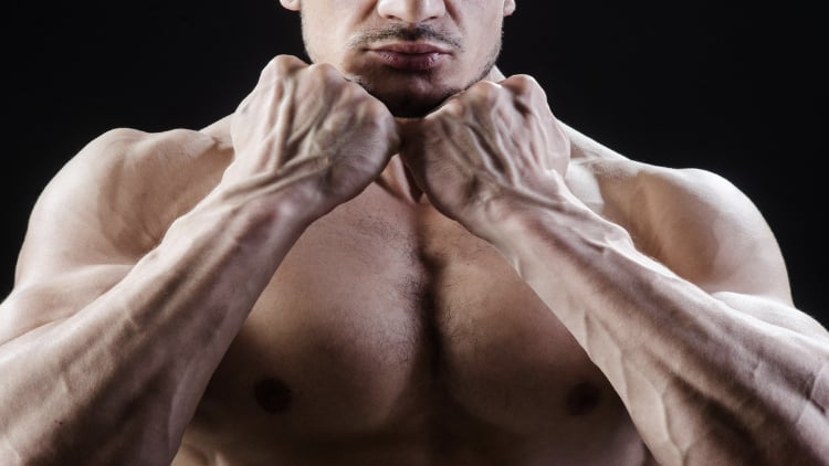 Fitness model showing his fists and forearms