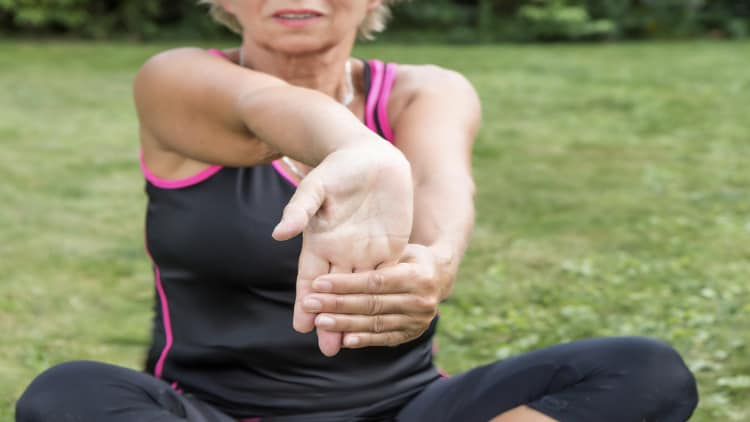 Woman stretching her forearm outside
