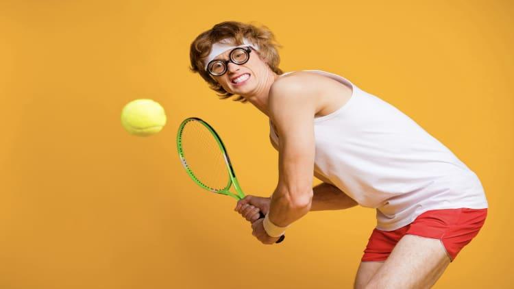 Geeky tennis player swinging his racket
