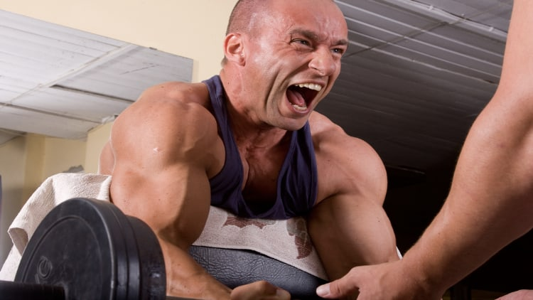 A man performing a hardcore bicep workout with his spotter