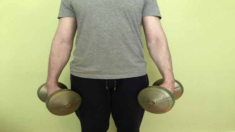 A man holding dumbbells by his sides