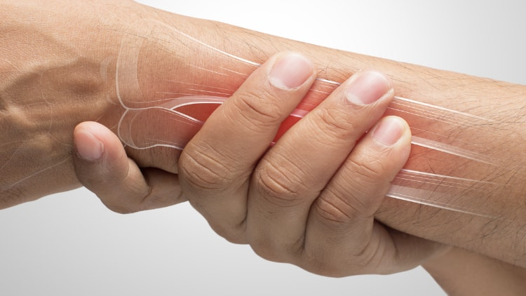 Person clutching their painful wrist