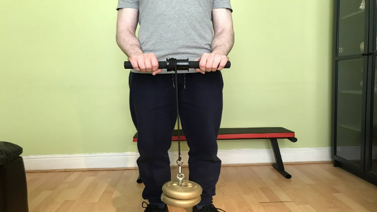 A person showing people how to use a wrist roller correctly
