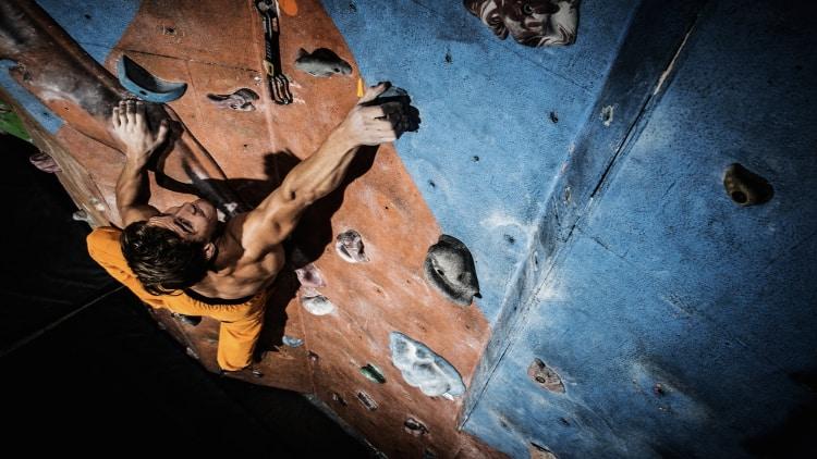Muscular man doing indoor rock climbing