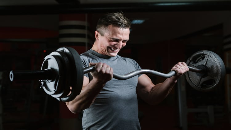 Man performing EZ bar curls with an intense expression