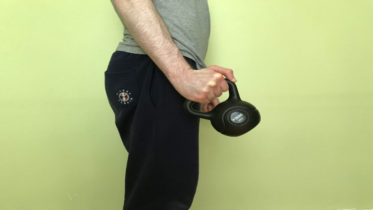 A man performing a kettlebell radial deviation exercise