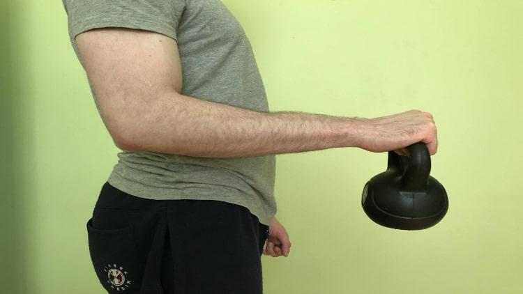 A man performing a kettlebell reverse curl