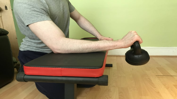 A man performing a kettlebell reverse wrist curl